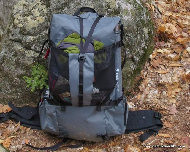 The rear pocket has heavy duty mesh so you can see the contents. It cinches shut with a elastic cordlock along the top and is further secured by the top Y strap